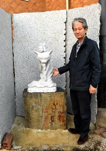 御影石でできた化け猫の像と小野修平さん=愛知県岡崎市