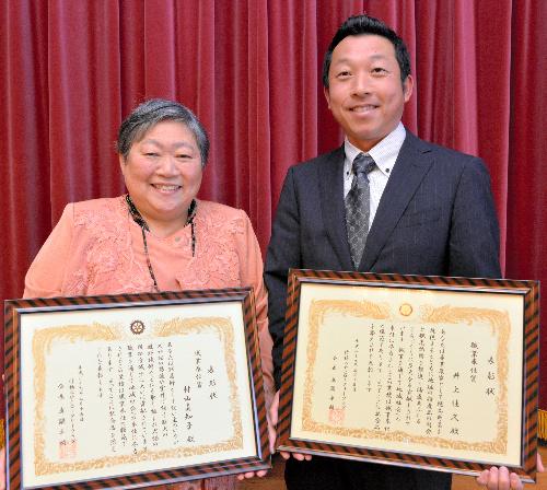 職業奉仕賞の表彰状を持つ村山真知子さん(左)と井上佳久さん=福岡県行橋市
