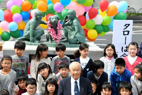 銅像「みんなのタロー」の前で記念撮影する橋本千代寿さん(手前中央)ら=JR石岡駅前